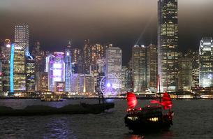 香港・九龍から香港島を望むビクトリア湾の夜景。船は観光ジャンク船「アクアルナ」の写真素材 [FYI03417176]