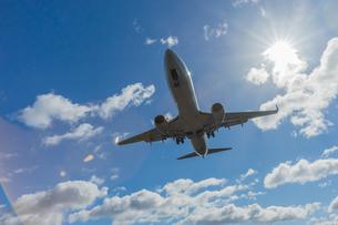 青空の下で飛行機が飛ぶ様子の写真素材 [FYI03418262]