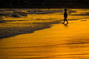 夕暮れの波打ち際で遊ぶ子供の写真素材 [FYI03418887]