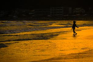 夕暮れの波打ち際で遊ぶ子供の写真素材 [FYI03418908]