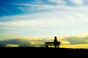 夕焼けの丘に座る女性のシルエットの写真素材 [FYI03418955]