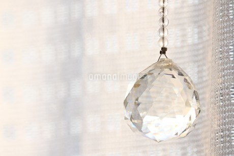 カーテンの手前に吊るされたサンキャッチャーの写真素材 [FYI03420119]
