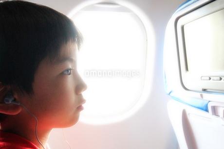 飛行機でモニターを見る子供の写真素材 [FYI03420120]