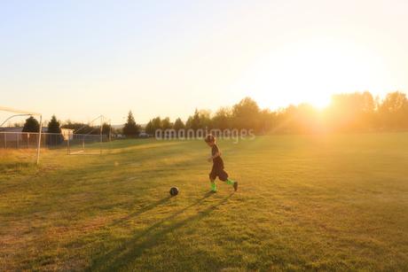 夕日の中でサッカーボールを蹴る少年の写真素材 [FYI03420125]