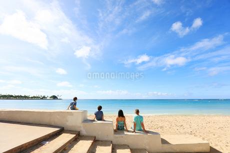 ハワイの海とハワイの空を見る男の子二人の家族の写真素材 [FYI03420143]