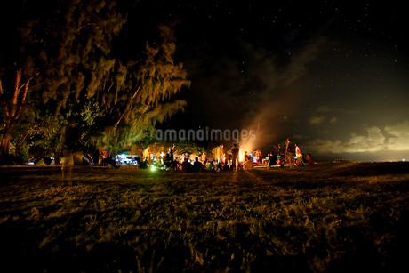 星空の下でグループで集まるキャンプファイヤーの写真素材 [FYI03420151]