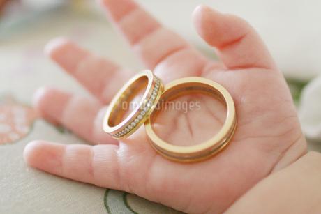 パパとママの指輪を持つ赤ちゃんの手の写真素材 [FYI03420153]