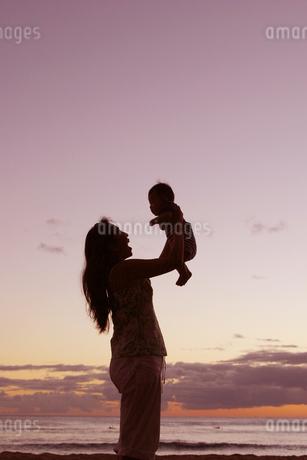 サンセットで赤ちゃんを高い高いするママの写真素材 [FYI03420154]