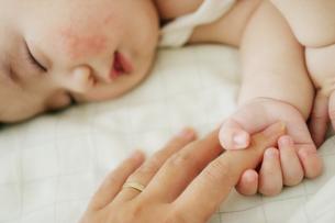 赤ちゃんがママの指をにぎって昼寝。の写真素材 [FYI03420156]