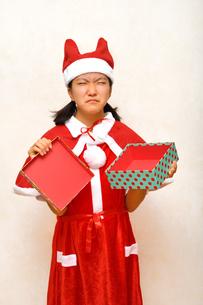 プレゼントを開けるサンタクロース衣装の女の子の写真素材 [FYI03420364]