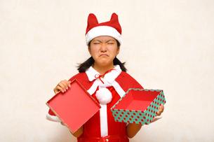 プレゼントを開けるサンタクロース衣装の女の子の写真素材 [FYI03420365]