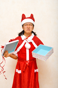プレゼントを開けるサンタクロース衣装の女の子の写真素材 [FYI03420366]