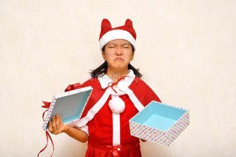 プレゼントを開けるサンタクロース衣装の女の子の写真素材 [FYI03420367]