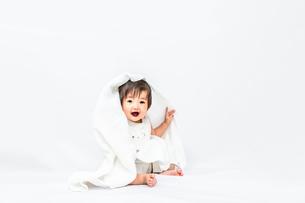 白背景でバスタオルを被りカメラ目線で微笑む女の子の赤ちゃんの写真素材 [FYI03420543]