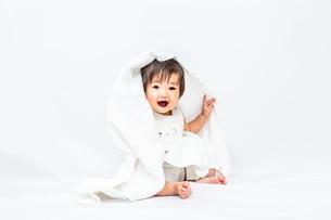 白背景でバスタオルを被りカメラ目線で微笑む女の子の赤ちゃんの写真素材 [FYI03420544]