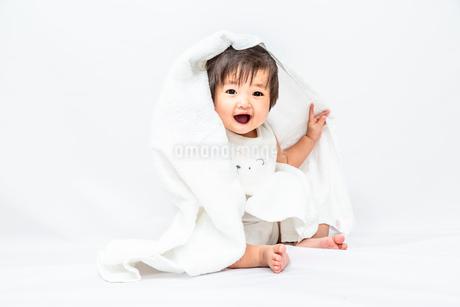 白背景でバスタオルを被りカメラ目線で微笑む女の子の赤ちゃんの写真素材 [FYI03420545]