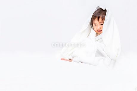 白背景でバスタオルを被り下目線の女の子の赤ちゃんの写真素材 [FYI03420546]