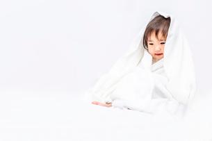 白背景でバスタオルを被り下目線の女の子の赤ちゃんの写真素材 [FYI03420547]