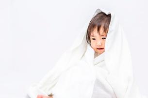 白背景でバスタオルを被り下目線の女の子の赤ちゃんの写真素材 [FYI03420548]