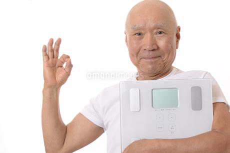笑顔のシニアと体重計の写真素材 [FYI03421604]