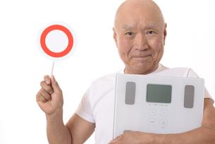 笑顔のシニアに体重計と丸バツ印の写真素材 [FYI03421605]