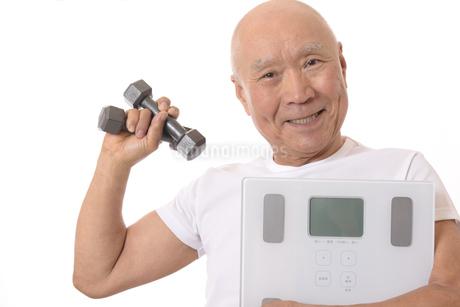 笑顔のシニアに体重計とダンベルの写真素材 [FYI03421607]