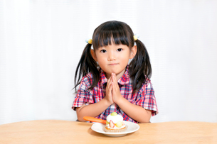 白背景でおやつのケーキを食べる前に「頂きます」をする幼い女の子。躾、マナー、行儀、幸せイメージの写真素材 [FYI03421673]