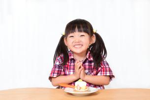 白背景でおやつのケーキを食べる前に「頂きます」をする幼い女の子。躾、マナー、行儀、幸せイメージの写真素材 [FYI03421674]