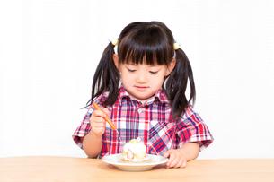 白背景でおやつのケーキを楽しそうに食べる幼い女の子。幸せ、成長、健康イメージの写真素材 [FYI03421675]