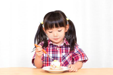 白背景でおやつのケーキを楽しそうに食べる幼い女の子。幸せ、成長、健康イメージの写真素材 [FYI03421676]