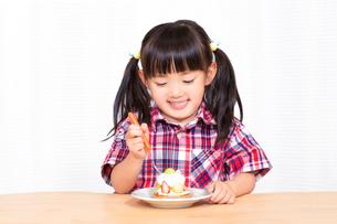 白背景でおやつのケーキを楽しそうに食べる幼い女の子。幸せ、成長、健康イメージの写真素材 [FYI03421677]