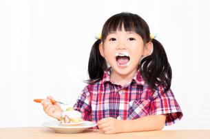 白背景でおやつのケーキを楽しそうに食べる幼い女の子。幸せ、成長、健康イメージの写真素材 [FYI03421678]