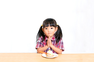 白背景でおやつのケーキを食べる前に「頂きます」をする幼い女の子。躾、マナー、行儀、幸せイメージの写真素材 [FYI03421679]