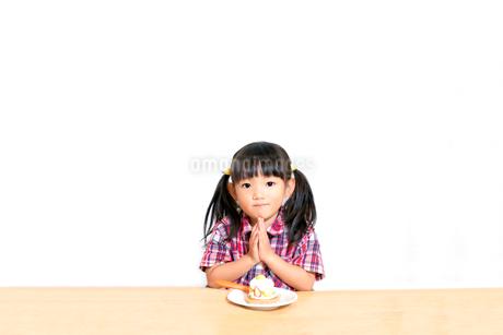 白背景でおやつのケーキを食べる前に「頂きます」をする幼い女の子。躾、マナー、行儀、幸せイメージの写真素材 [FYI03421680]