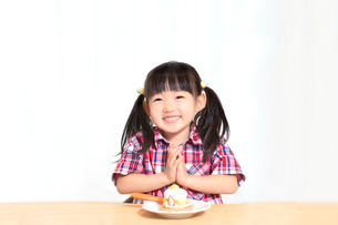 白背景でおやつのケーキを食べる前に「頂きます」をする幼い女の子。躾、マナー、行儀、幸せイメージの写真素材 [FYI03421681]