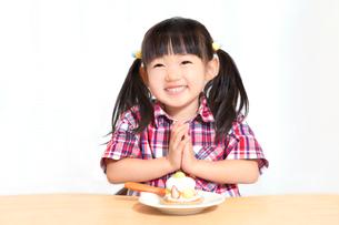 白背景でおやつのケーキを食べる前に「頂きます」をする幼い女の子。躾、マナー、行儀、幸せイメージの写真素材 [FYI03421682]