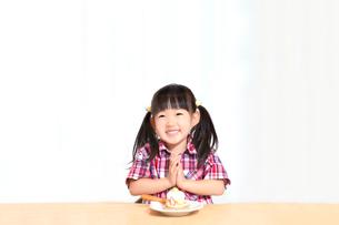 白背景でおやつのケーキを食べる前に「頂きます」をする幼い女の子。躾、マナー、行儀、幸せイメージの写真素材 [FYI03421683]