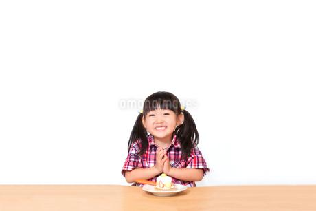 白背景でおやつのケーキを食べる前に「頂きます」をする幼い女の子。躾、マナー、行儀、幸せイメージの写真素材 [FYI03421684]