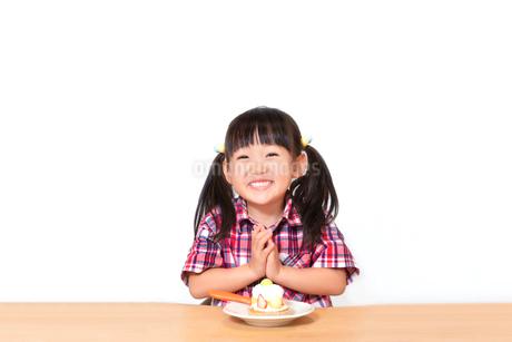 白背景でおやつのケーキを食べる前に「頂きます」をする幼い女の子。躾、マナー、行儀、幸せイメージの写真素材 [FYI03421685]