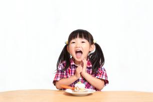 白背景でおやつのケーキを食べる前に「頂きます」をする幼い女の子。躾、マナー、行儀、幸せイメージの写真素材 [FYI03421686]