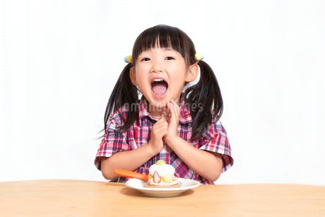 白背景でおやつのケーキを食べる前に「頂きます」をする幼い女の子。躾、マナー、行儀、幸せイメージの写真素材 [FYI03421687]