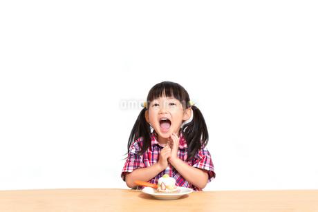 白背景でおやつのケーキを食べる前に「頂きます」をする幼い女の子。躾、マナー、行儀、幸せイメージの写真素材 [FYI03421688]
