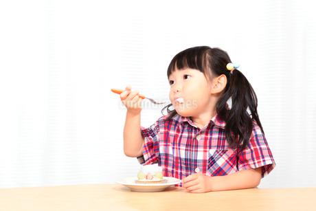 白背景でおやつのケーキを楽しそうに食べる幼い女の子。幸せ、成長、健康イメージの写真素材 [FYI03421689]