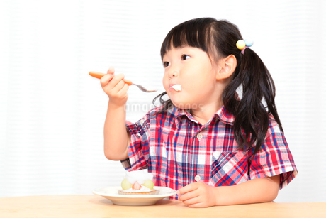 白背景でおやつのケーキを楽しそうに食べる幼い女の子。幸せ、成長、健康イメージの写真素材 [FYI03421690]