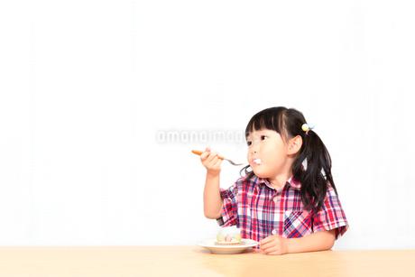 白背景でおやつのケーキを楽しそうに食べる幼い女の子。幸せ、成長、健康イメージの写真素材 [FYI03421691]