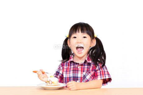 白背景でおやつのケーキを楽しそうに食べる幼い女の子。幸せ、成長、健康イメージの写真素材 [FYI03421693]