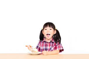 白背景でおやつのケーキを楽しそうに食べる幼い女の子。幸せ、成長、健康イメージの写真素材 [FYI03421695]