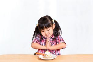 白背景でおやつのケーキを食べる前に「頂きます」をする幼い女の子。躾、マナー、行儀、幸せイメージの写真素材 [FYI03421696]