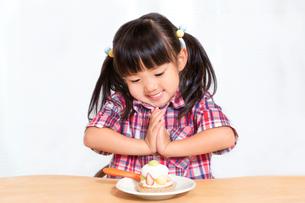 白背景でおやつのケーキを食べる前に「頂きます」をする幼い女の子。躾、マナー、行儀、幸せイメージの写真素材 [FYI03421697]