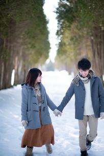 雪道で手をつなぐカップルの写真素材 [FYI03421978]